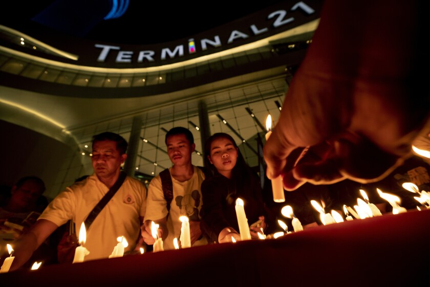 People attend a memorial service at the Terminal 21 Korat shopping mall in Thailand following a Feb. 8 mass shooting.