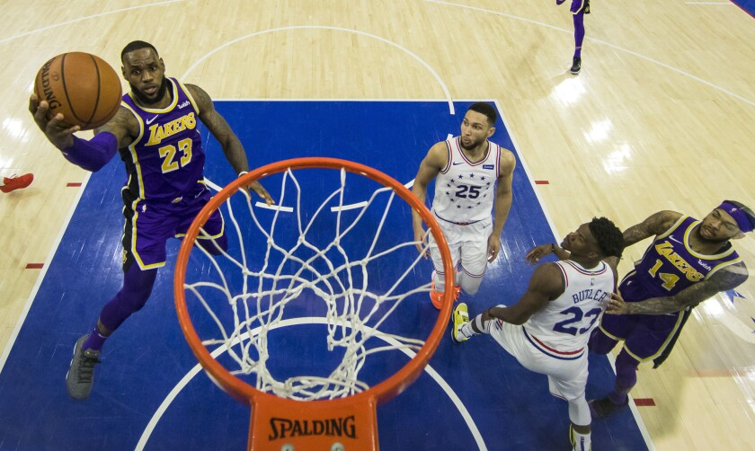 Los Angeles Lakers' LeBron James, left, goes up for the shot as Philadelphia 76ers' Ben Simmons, center, of Australia, and Jimmy Butler, right, look on during the second half of an NBA basketball game, Sunday, Feb. 10, 2019, in Philadelphia. The 76ers won 143-120.
