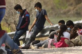 MISSION, TEXAS -Asylum seekers who crossed the US - Mèxic border illegally wait to be processed outside Mission, Texas on March 17, 2020: Wednesday, March 17, 2021 in Mission, Texas. (Carolyn Cole / Los Angeles Times)