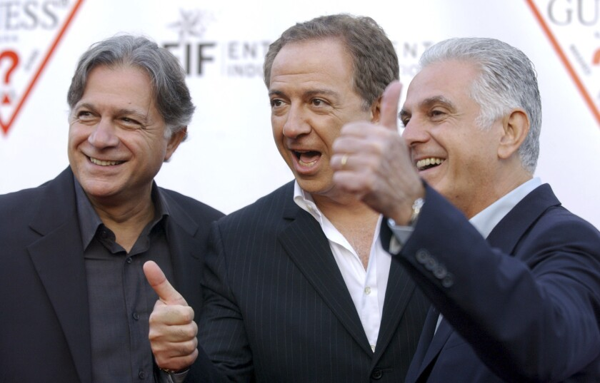 In this May 9, 2002 file photo, Guess Inc. founders and brothers, from left, Armand, Paul and Maurice Marciano arrive at the company's 20th anniversary party in Los Angeles. Guess Inc. says its co-founder Paul Marciano is stepping down after a company-commissioned investigation of allegations of sexual harassment and assault.