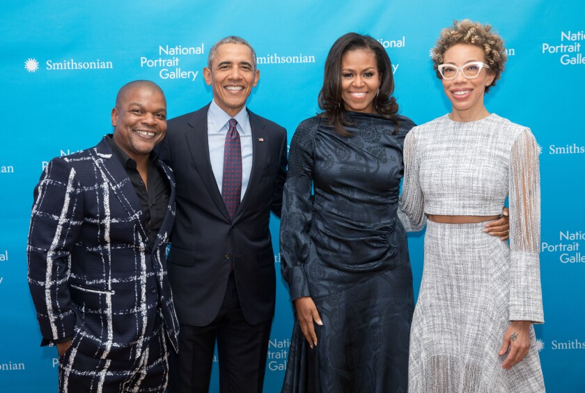 Artist Kehinde Wiley, left, stands next to former President Barack Obama, whose portrait he painted. Amy Sherald, right, painted former First Lady Michelle Obama.