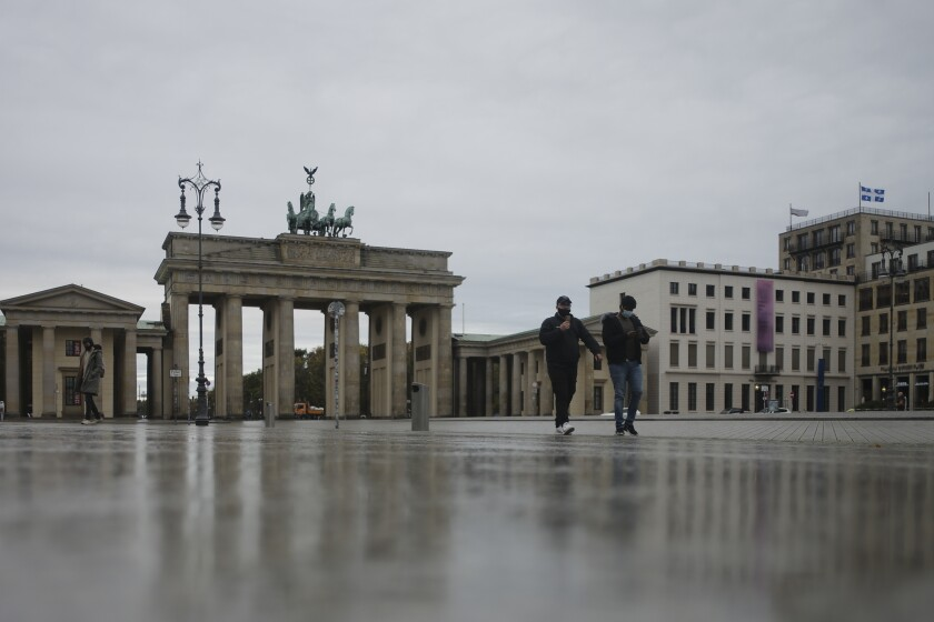 Teo man with face maskes cross the desrted Pariser Platz in front of the Brandenburg Gate, a tourist highlight, in Berlin, Germany, Monday, Nov. 2, 2020. New measures to stop the spread of the coronavirus come into force today in Germany. (AP Photo/Markus Schreiber)