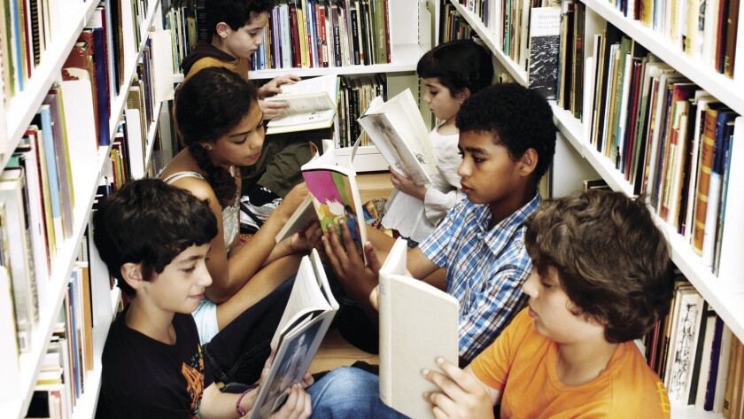 Kids reading books in a library