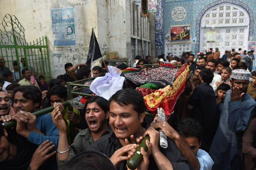 Mourners on Feb. 17 carry the coffin of a victim killed in a suicide bombing at a Sufi shrine in Pakistan's Sindh province.