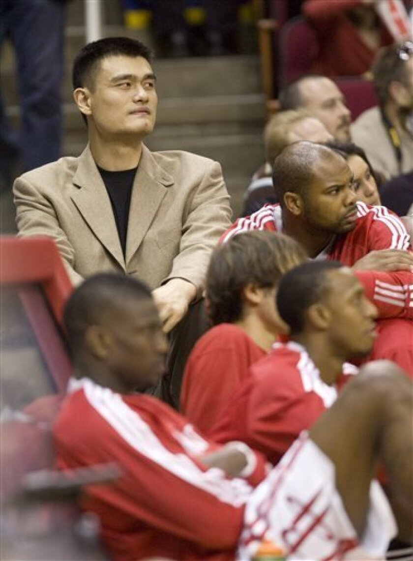Houston Rockets center Yao Ming, left, watches his teammates during an NBA preseason basketball game against the Cleveland Cavaliers on Sunday, Oct. 10, 2010, in Houston. (AP Photo/Steve Campbell)