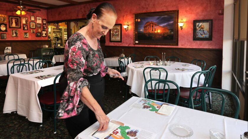 At Feliccia's Italian Restaurant and Deli waitress Beverly Stavron sets tables for dinner. The place is closing December 13th. after 40 years in business.