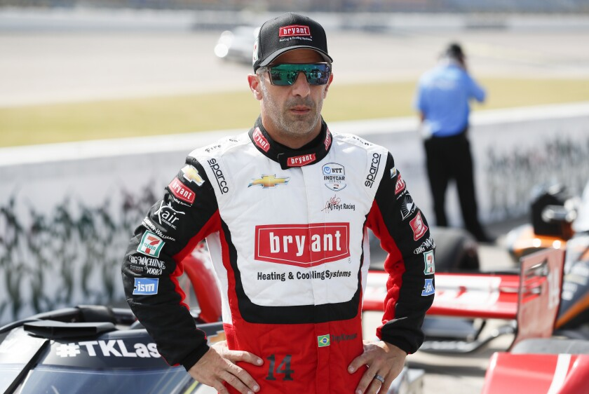 FILE - In this July 17, 2020, file photo, driver Tony Kanaan, of Brazil, stands next to his car during qualifying for an IndyCar Series auto race at Iowa Speedway in Newton, Iowa. Kanaan's supposed farewell tour last year fizzled amid nearly empty tracks. Then he was given another chance to extend his IndyCar career, this time before fans. His first two races come this weekend at Texas Motor Speedway. (AP Photo/Charlie Neibergall, File)