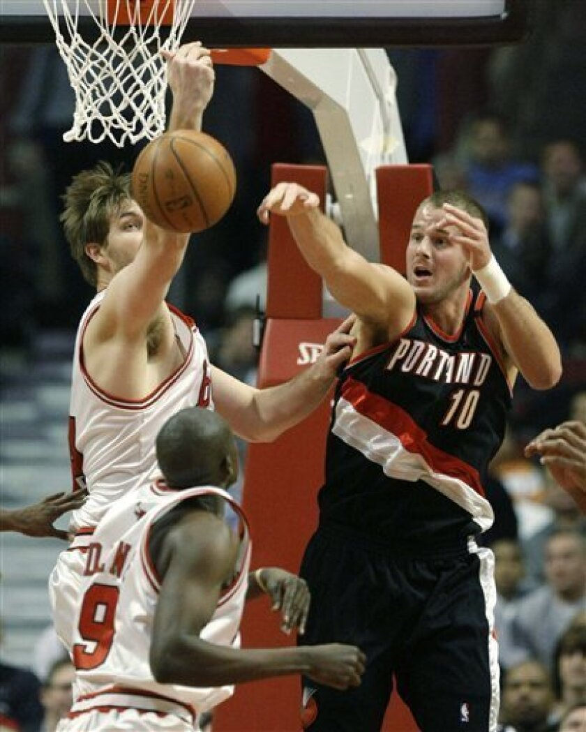Chicago Bulls forward Luol Deng (9) of Sudan has his shot blocked by Portland Trail Blazers center Joel Przybilla (10), as Chicago Bulls' Aaron Gray, left, tries to rebound, during the first half of their NBA basketball game in Chicago, Monday, Jan. 12, 2009, (AP Photo/Charles Rex Arbogast)