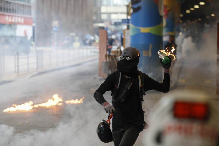 A protester prepares to throw Molotov cocktail in Hong Kong on Sunday.