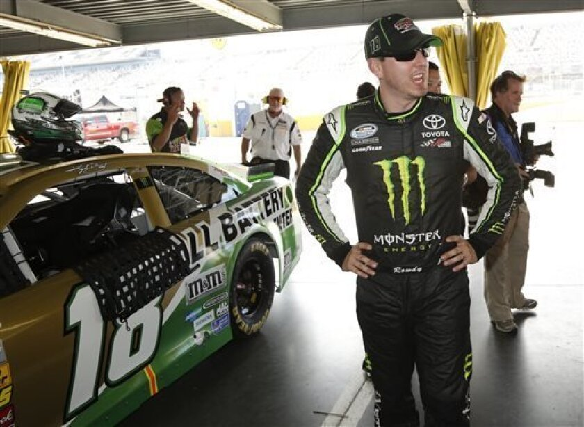 Kyle Busch stands by his car in the garage after qualifying for the pole position for Saturday's NASCAR Sprint Cup auto race at Daytona International Speedway, Friday, July 5, 2013, in Daytona Beach, Fla. (AP Photo/Reinhold Matay)