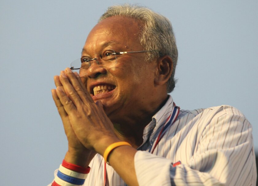 """Thai anti-government protest leader Suthep Thaugsuban gives a Thai tradition way of greeting """"wai"""", addressing his supporters at the Government House following a march rally Monday, Dec. 9, 2013 in Bangkok, Thailand. Desperate to defuse Thailand's deepening political crisis, Prime Minister Yingluck Shinawatra on Monday said she is dissolving the lower house of Parliament and called for early elections. But the moves did nothing to stem a growing tide of more than 150,000 protesters vowing to overthrow her in one of the nation's largest demonstrations in years.(AP Photo/Sakchai Lalit)"""