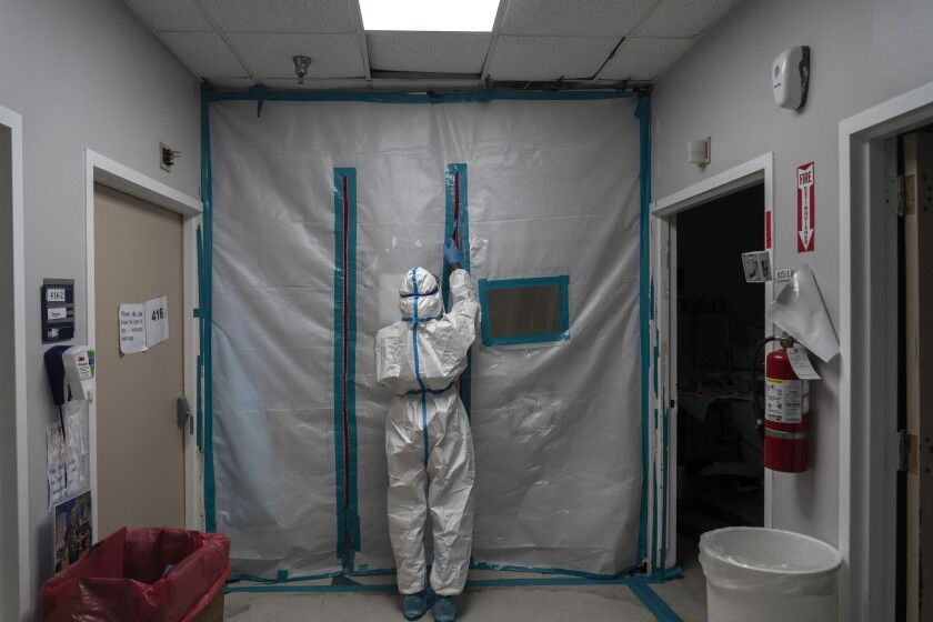 A medical staff member in a white protective suit zips closed the barrier on a COVID-19 intensive care unit