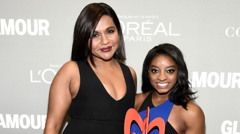 Mindy Kaling, left, and honoree Simone Biles pose with an award at the Glamour Women of the Year event at NeueHouse Hollywood.
