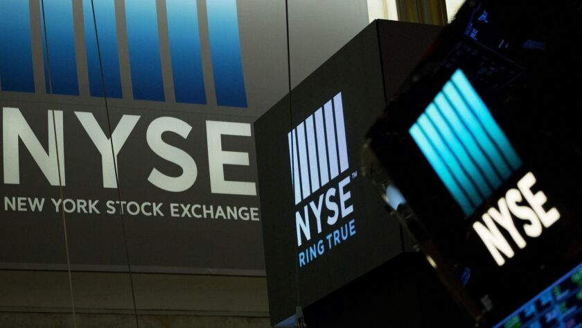 FILE- In this May 10, 2018, file photo, signs for the New York Stock Exchange hang above the trading
