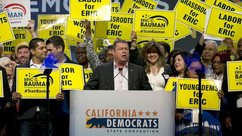 Surrounded by supporters, Eric Bauman, center, who is running to head the California Democratic Part