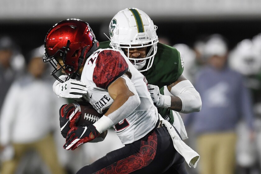 Aztecs back Chase Jasmin (22) is tackled by Colorado State's Jamal Hicks in the second quarter.
