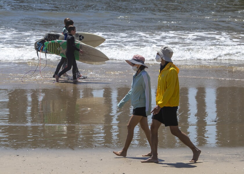 A trio of young surfers walks past a couple wearing protective masks as beachgoers enjoy summer-like weather April 22 in Huntington Beach.
