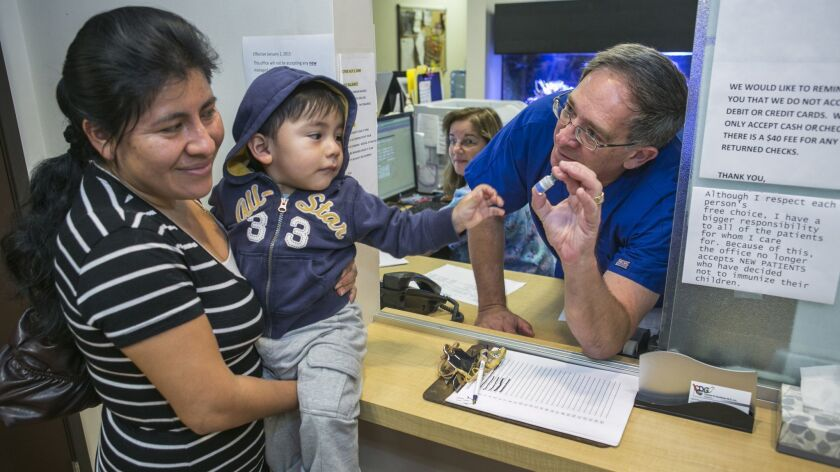 Charles Goodman talks with patient Carmen Lopez, 37, holding her 18-month-old son, Daniel, after being vaccinated with the measles-mumps-rubella vaccine, or MMR, at his practice in Northridge.