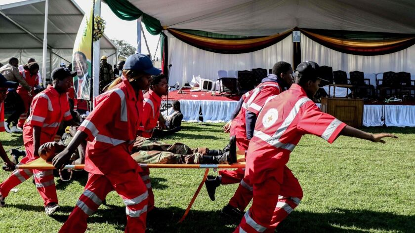 Injured people are evacuated after an explosion at the stadium in Bulawayo where Zimbabwe's president had just addressed a rally on June 23.