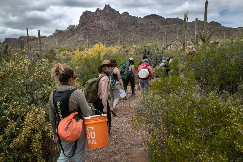 Volunteers for the humanitarian aid organization No More Deaths walk with buckets of food and jugs of water for undocumented immigrants on May 10 near Ajo, Arizona.