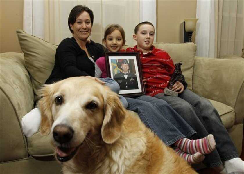 """Kimberly Hazelgrove, with her children Katelyn Hazelgrove, 6, and Brandon Hazelgrove, 9, with their dog """"Molly"""" pose for a picture in their home in Lorton, Va., Tuesday, Feb. 2, 2010. Kimberly's husband U.S. Army Chief Warrant Officer Brian Hazelgrove died in Iraq in 2004. For a decade, war widows in matching yellow suit jackets and hats quietly and persistently have knocked on Capitol Hill doors seeking an end to the """"widows' tax,"""" a government policy that deprives them of benefits from their husbands' military service. (AP Photo/Alex Brandon)"""