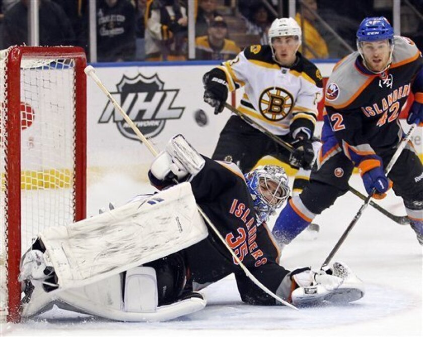 New York Islanders Dylan Reese (42) looks on as goalie Al Montoya (35) stops a shot on goal by the Boston Bruins during the first period of an NHL hockey game at the Nassau Coliseum in Uniondale, N.Y., Saturday, March 31, 2012. (AP Photo/Paul J. Bereswill)
