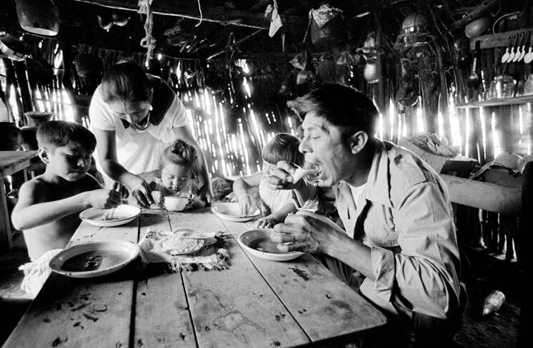 Tortillas wrapped in a cloth to keep them warm and placed in the center of the table. Portions of tortillas are used as spoons for scooping the black bean soup. Dario and Herculana and their family in their kitchen. Chichimilá, Yucatán, 1976.
