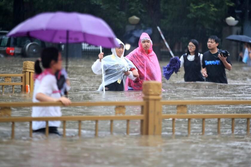 Personas caminan en calles inundadas en Zhengzhou, provincia de Henan, China, el martes 20 de julio de 2021.