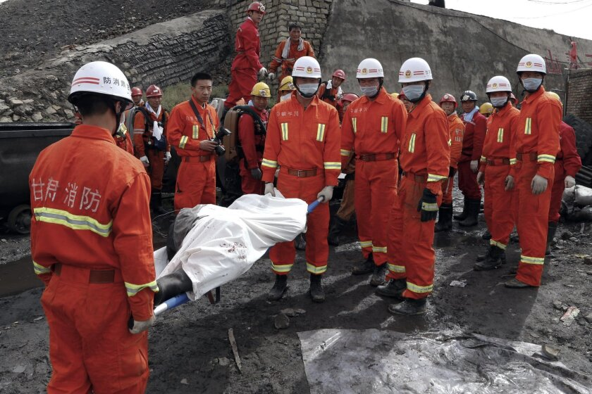 FILE - In this Sept. 25, 2012 file photo, firemen carry a stretch with a body of a dead miner at a coal mine in Baiyin city, in northwestern China's Gansu province. Chinese authorities say mine safety improved significantly in 2013 as the numbers in mine incidents, fatalities and missing persons dropped. (AP Photo/File) CHINA OUT
