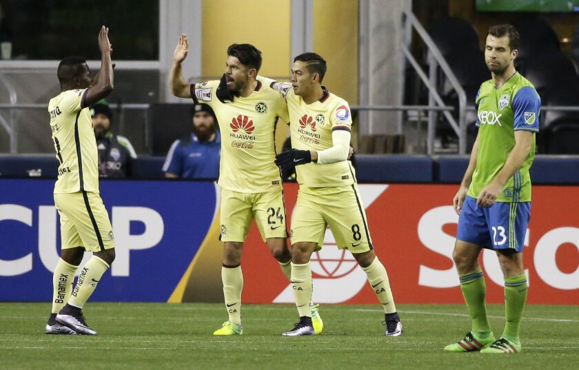 Club America forward Oribe Peralta, second from left, is greeted by teammates Darwin Quintero, left, and Andres Andrade as Seattle Sounders midfielder Andreas Ivanshitz walks past after Peralta scored a goal during the second half of a CONCACAF Champions League soccer quarterfinal, Tuesday, Feb. 23, 2016, in Seattle. The match ended in a 2-2 tie. (AP Photo/Ted S. Warren)
