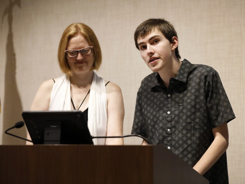 Elliot Sylvester, 18, accompanied by his communication partner, Julie Sando, left, presents a pre-recorded speech at a graduation ceremony for Good Dog! Autism Companions on Saturday in La Jolla. Elliot's parents, Laura and Rick Sylvester, started Good Dog! after seeing how a service dog helped their son, who is on the autism spectrum.