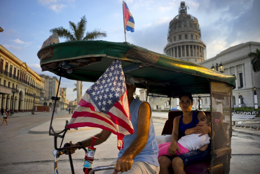 A taxi pedals his bicycle, decorated with Cuban and U.S. flags, as he transports a woman holding a sleeping girl, near the Capitolio in Havana, Cuba.