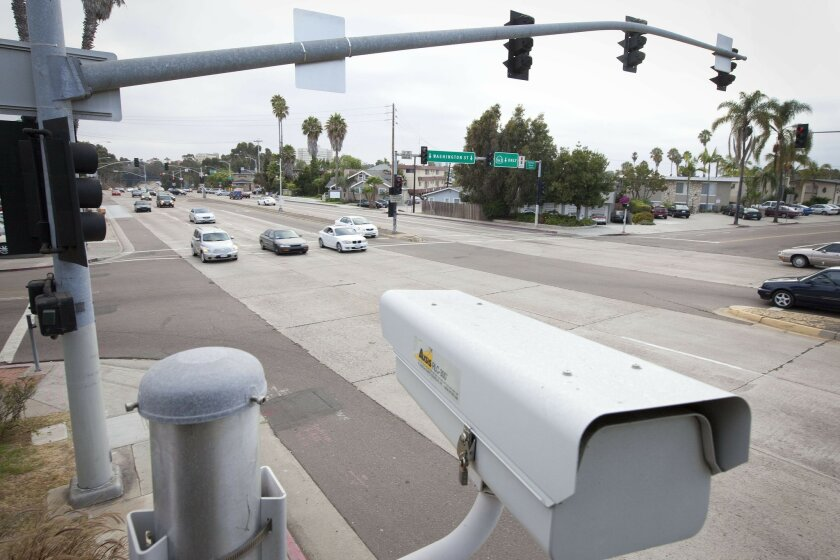 Cars passing the red-light cameras at Mission Center Road and Camino Del Rio North.