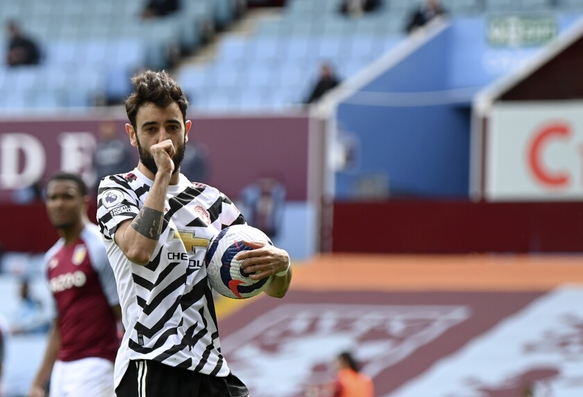 Manchester United's Bruno Fernandes celebrates after scoring his side's opening goal from penalty during the English Premier League soccer match between Aston Villa and Manchester United at Villa Park in Birmingham, England, Sunday, May 9, 2021. (Shaun Botterill/Pool via AP)