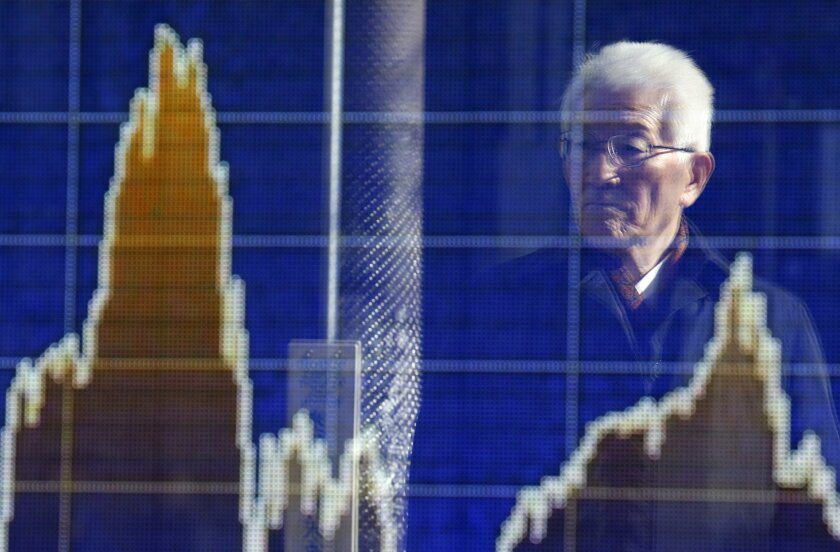 A man is reflected on the electronic board of a securities firm in Tokyo, Wednesday, Feb. 17, 2016. Asian stock markets were mostly higher Wednesday as investors weighed the potential outcome of a preliminary agreement between Russia and Saudi Arabia to hold off on further increases in crude oil pr