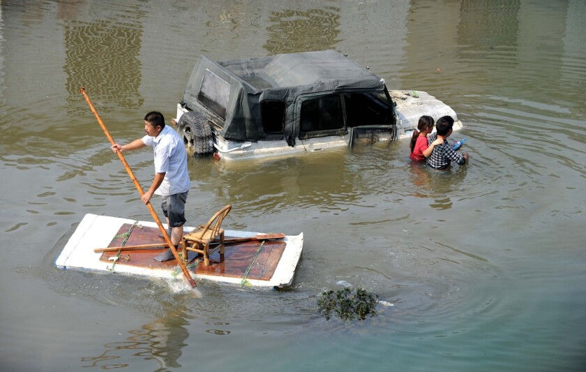 A makeshift raft joins the traffic on a flooded street in Yuyao, China. At least 10 people were killed and five missing after Typhoon Fitow hit eastern China.