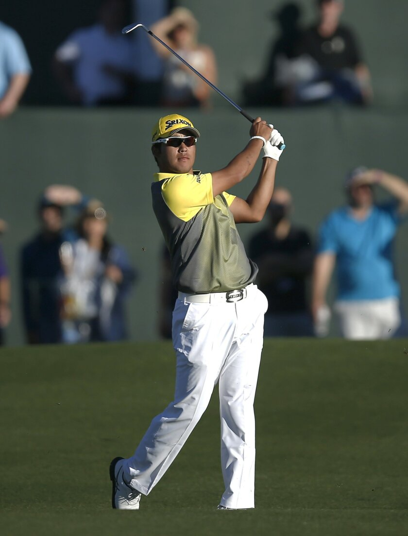 Hideki Matsuyama hits his approach shot on the second hole of a sudden death playoff during the Phoenix Open golf tournament, Sunday, Feb. 7, 2016, in Scottsdale, Ariz. Matsuyama defeated Rickie Fowler in the playoff. (AP Photo/Rick Scuteri)