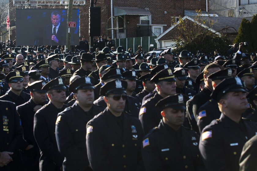Police officers turn their backs as New York City Mayor Bill de Blasio speaks at the funeral of New York City police officer Rafael Ramos in the Glendale section of Queens, Saturday, Dec. 27, 2014, in New York. Ramos and his partner, officer Wenjian Liu, were killed Dec. 20 as they sat in their pat