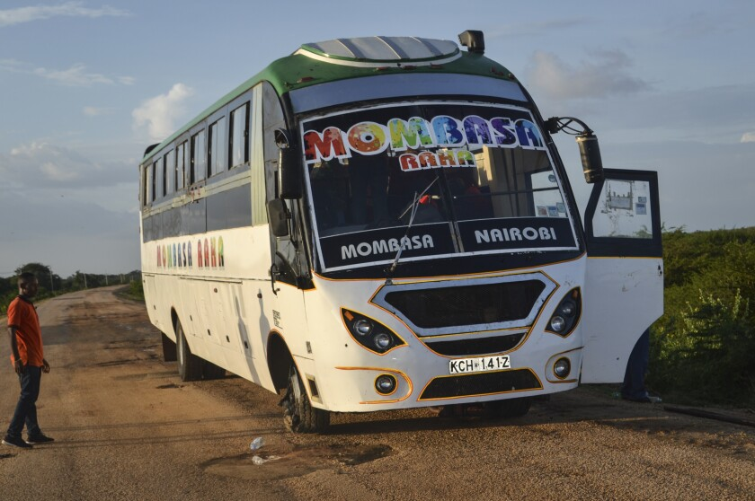 A man looks at a bus which was ambushed by gunmen in the Nyongoro area of Lamu county, near the Indian Ocean coast of Kenya Thursday, Jan. 2, 2020. Kenya police say four people have been killed on Thursday in two ambushes in which passenger buses in the country's eastern coastal area were fired on by gunmen, and for which Islamic extremist group al-Shabab claimed responsibility. (AP Photo)