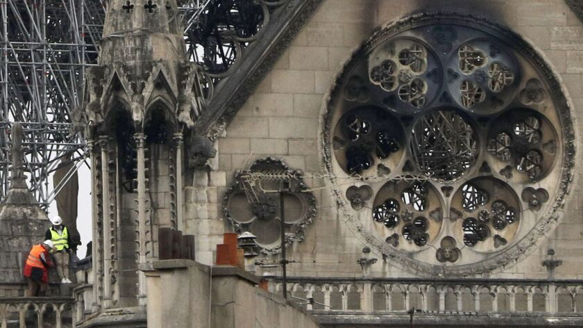 Experts inspect the damaged Notre Dame cathedral after the fire in Paris, Tuesday, April 16, 2019. E