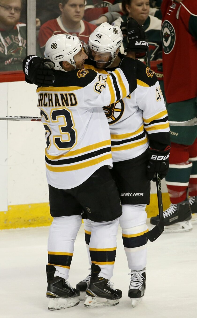 Boston Bruins left wing Brad Marchand (63) and teammate David Krejci (46), of the Czech Republic, celebrate Marchand's goal off Minnesota Wild goalie Darcy Kuemper during the first period of an NHL hockey game in St. Paul, Minn., Saturday, Feb. 13, 2016. (AP Photo/Ann Heisenfelt)