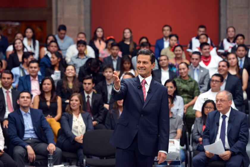 """El presidente de México, Enrique Peña Nieto (c), habla durante un diálogo con jóvenes sobre su cuarto informe de gobierno, presentado en la capital mexicana, donde negó categóricamente haber plagiado su tesis de licenciatura, si bien reconoció que pudo haber cometido """"algún error metodológico"""". EFE/Presidencia"""