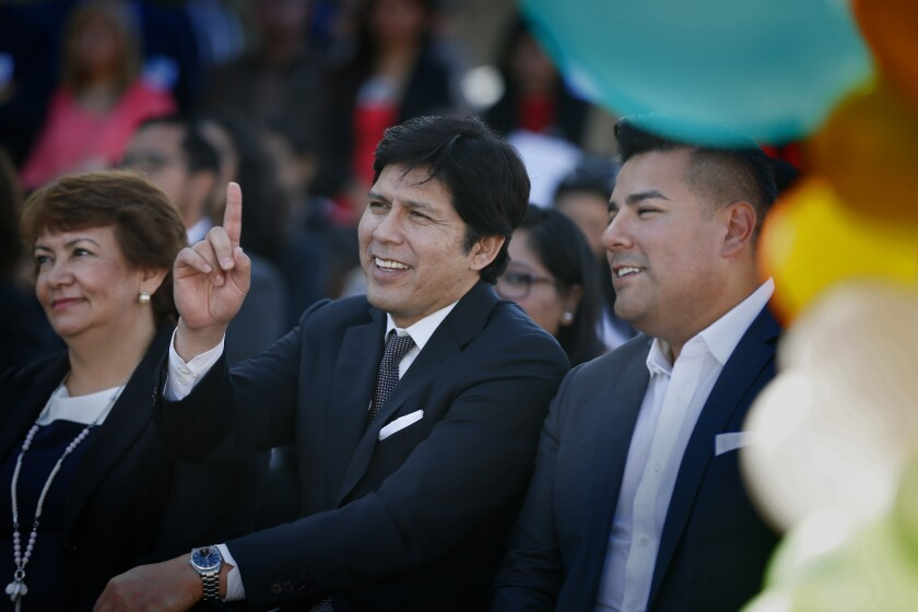 California Senate President Pro Tempore Kevin de León, center, with Sen. Ricardo Lara at a news conference celebrating the expansion of healthcare to children in the country illegally. At left is Arabella Aguirre, a Guatemala-born mother of three undocumented children who will benefit from the signing of the law.