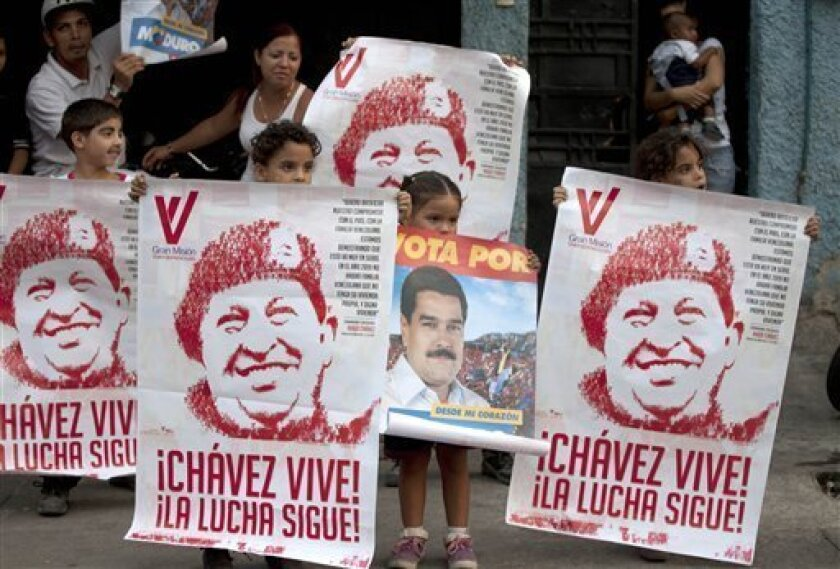 Children hold up posters of Venezuela's late President Hugo Chavez and one of ruling party candidate Nicolas Maduro as a campaign convoy drives along in Caracas, Venezuela, Wednesday, April 10, 2013. Maduro, the hand-picked successor of the late President Hugo Chavez, is running for president again