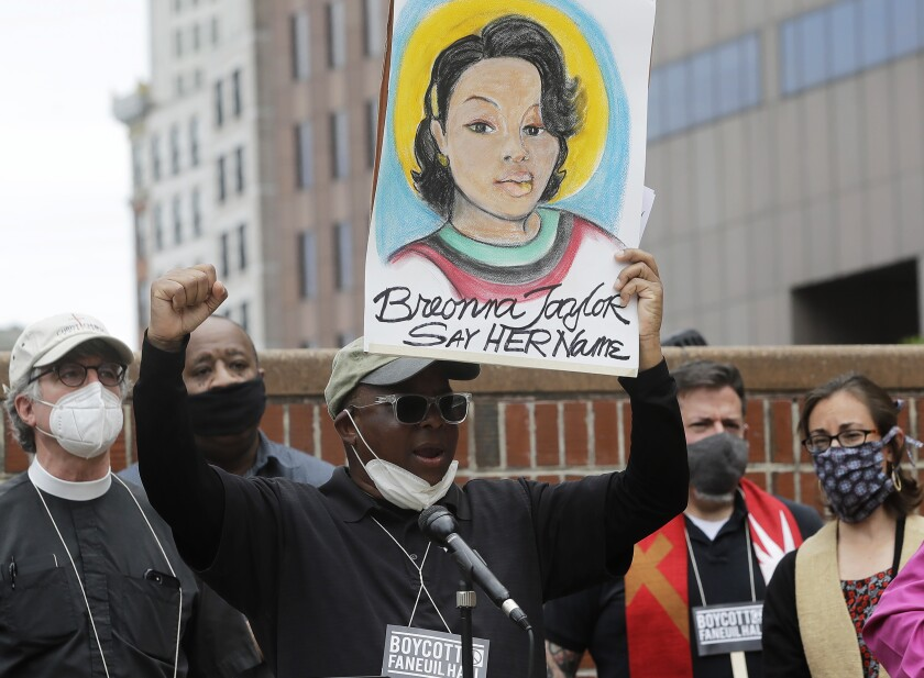 Kevin Peterson holds up a placard showing Breonna Taylor at a Boston rally on June 9.