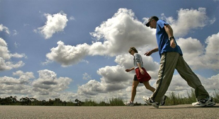 Scattered clouds provided a dramatic backdrop for walkers on the five-mile path around Lake Miramar yesterday. June's unusual, persistent weather pattern brought rain to some areas of the county overnight. (Howard Lipin / Union-Tribune)