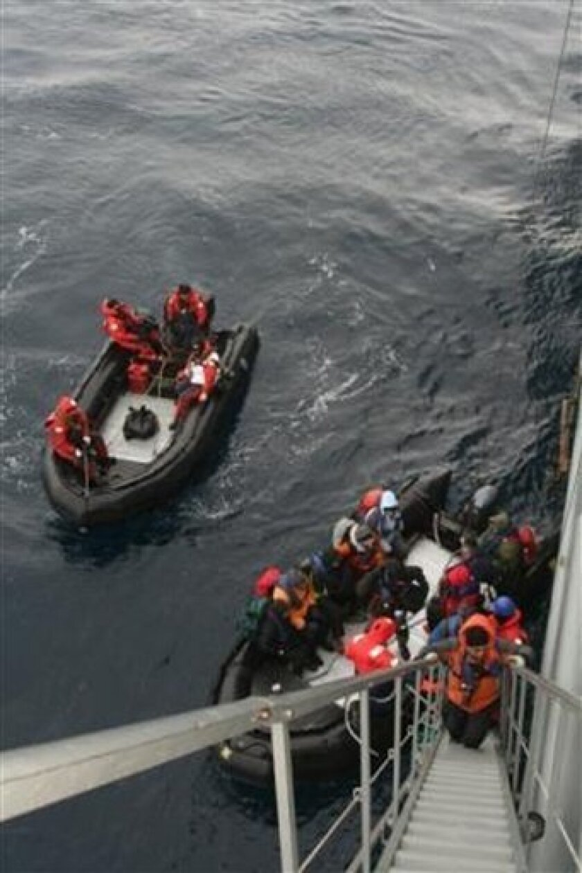 In this photo released by Chile's Army, passengers being rescued from a cruise ship that ran aground in the Antarctic a day earlier board a Chilean Navy ship, Friday, Dec. 5, 2008. The 89 passengers and 33 crew member aboard the Argentina-based Ushuaia were transported to the Chilean ship Aquiles, after the Ushuaia suffered cracks and started leaking fuel and taking on water on Thursday. Navy officials said the ship was never in danger of sinking and that all rescued passengers and crew members were in good condition and had been transported to the Antarctic Chilean base Presidente Frei. (AP Photo/Chilean Navy)
