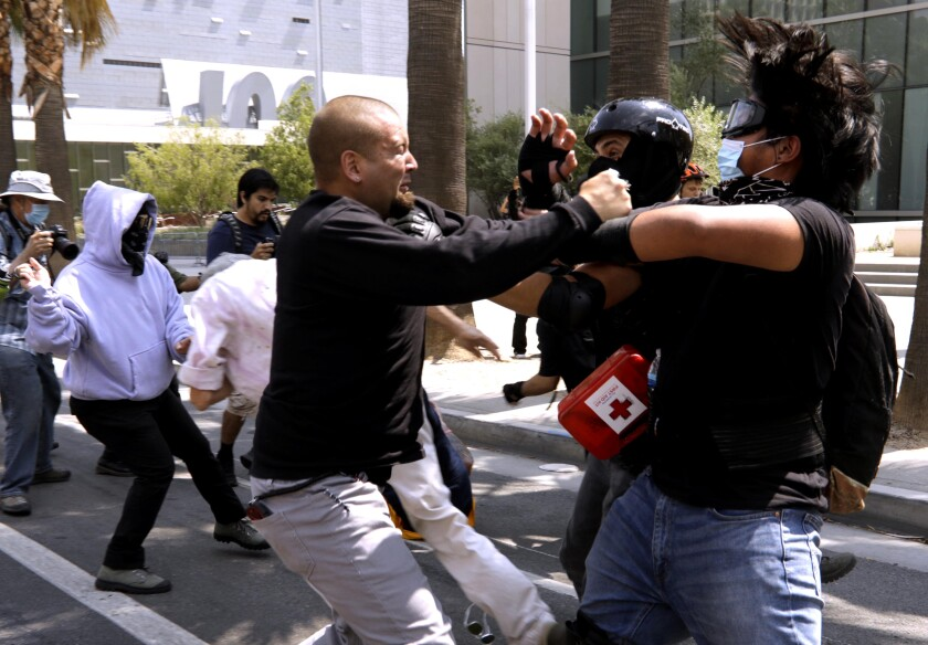 An anti-vax demonstrator confronts counterprotesters in front of Los Angeles Police Department headquarters on Saturday.