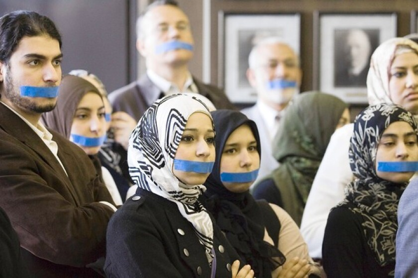 Irvine 11 supporters tape their mouths closed during a press conference Friday.