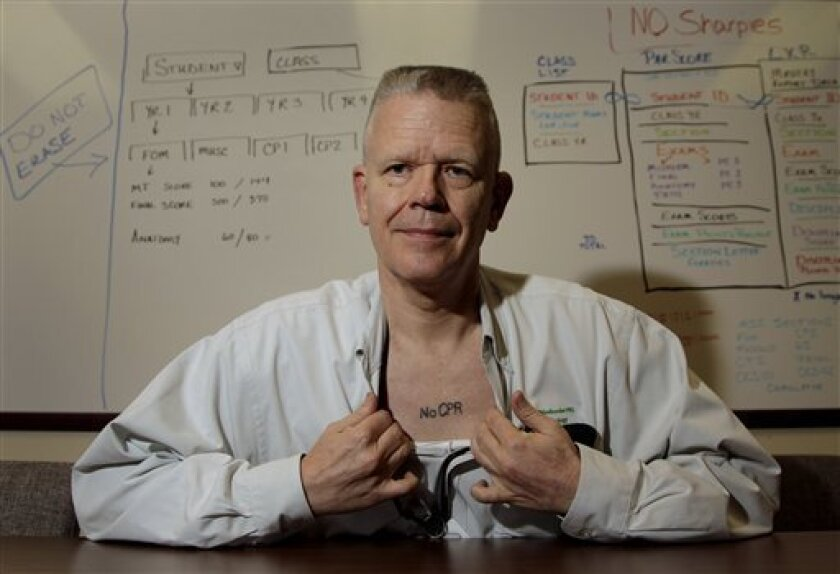 In this photo taken Sept. 29, 2011, Kansas City, Mo. pathologist Dr. Ed Friedlander displays his tattoo with a medical directive to not use CPR. Friedlander is among a growing number of people who are getting tattoos that tell doctors and first responders about their medical concerns, from chronic